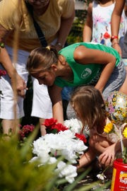 Evie Lewis, 10, center, and Ellie Reeves, 6, below, place flowers at a memorial outside the Ride the Ducks parking lot in Branson on Friday.