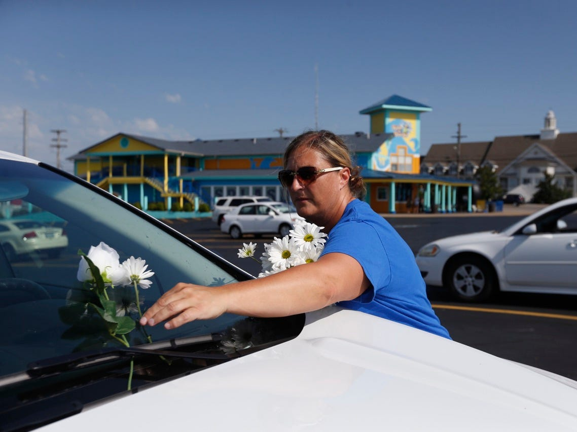 Ruth Ann Sanders, of Tennessee, places a flower on the windshield of a car in the Ride the Ducks parking lot in Branson on Friday.