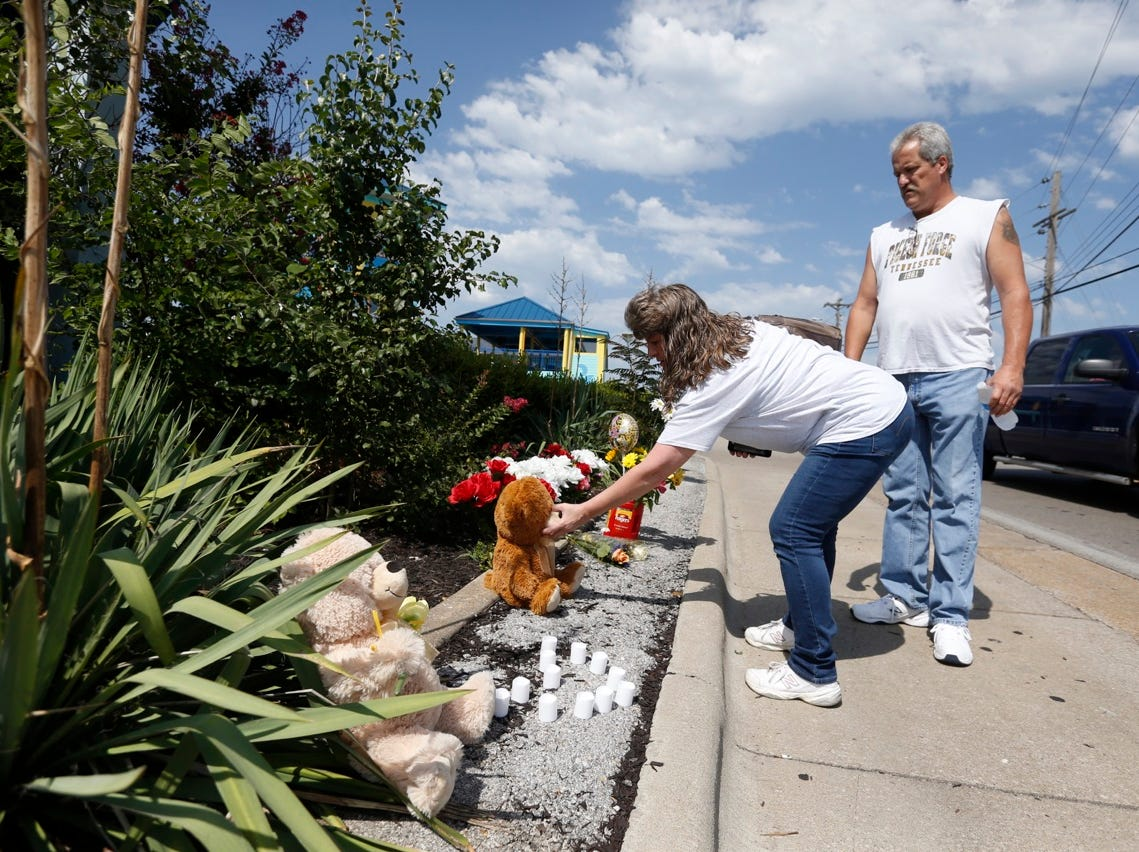 Dianne Lovell and her husband Jim Lovell place flowers and a teddy bear at a memorial outside Ride the Ducks in Branson on Friday.