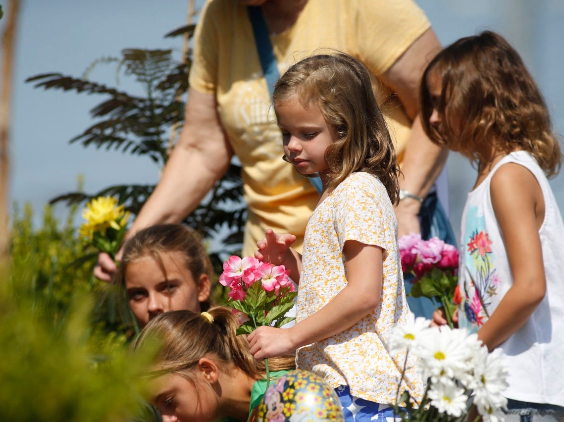 Ellie Reeves, 6, center, along with other members of her family place flowers at a memorial outside the Ride the Ducks parking lot in Branson on Friday.