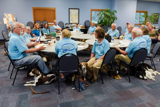 Members of the Central Minnesota Therapy Animal Association hold their monthly meeting while their certified therapy pets sit quietly Tuesday, July 17, at St.  John's Episcopal Church
