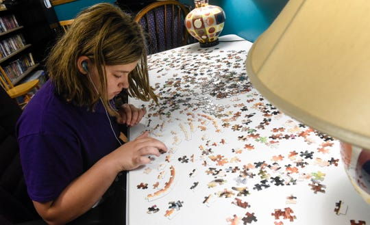 Paige Theisen works on a puzzle at the home of Glenn and Cathie Ahrensfeld Friday, July 20, in Sartell.