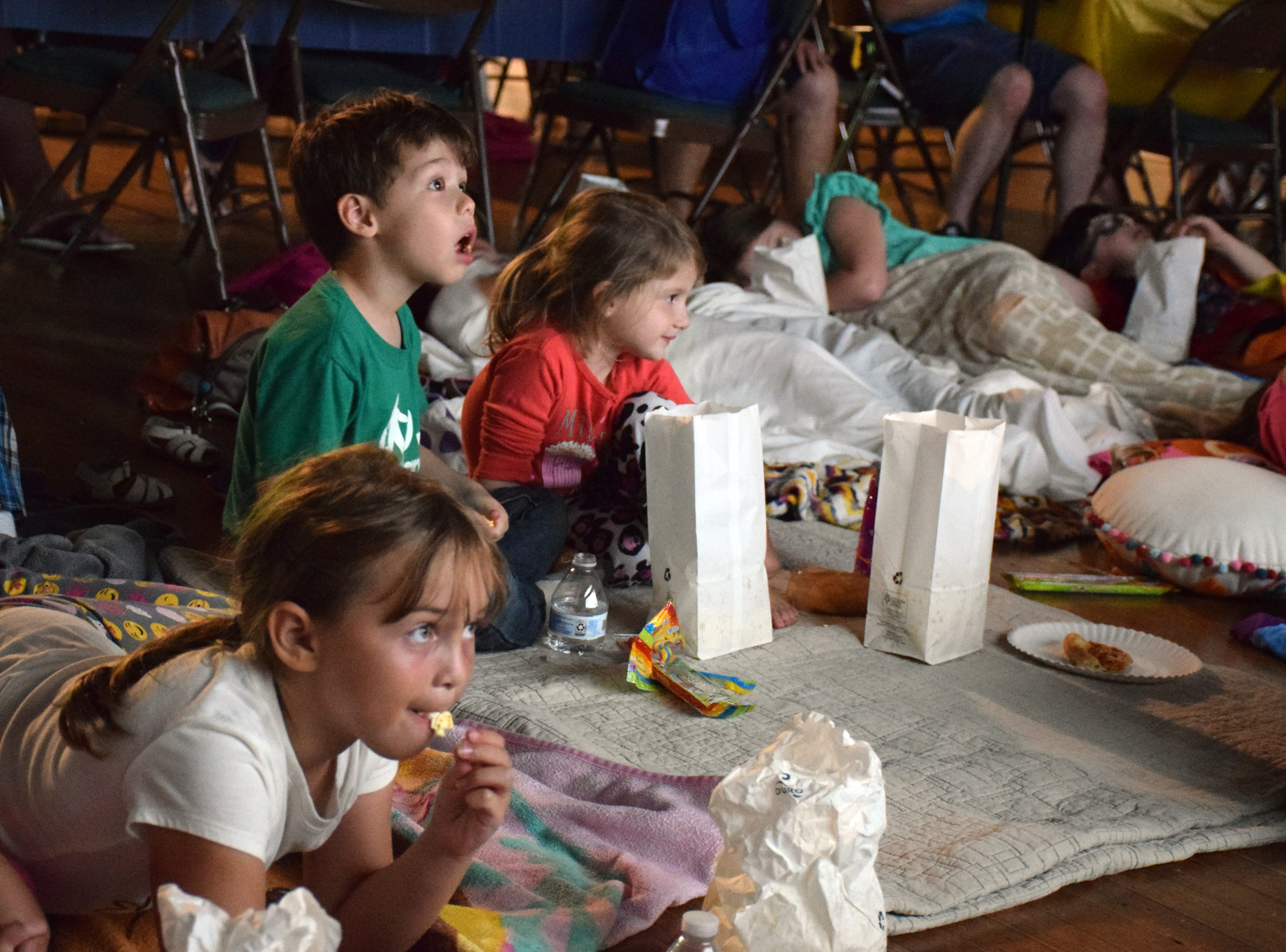 Children settle in to watch Inside Out family movie.