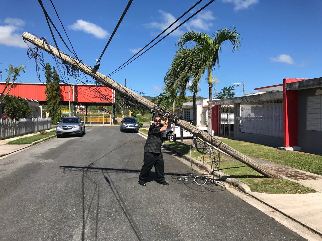 Marcos Flores pretending to hold up a hurricane-damaged fallen pole on the street of his family home in Juncos.