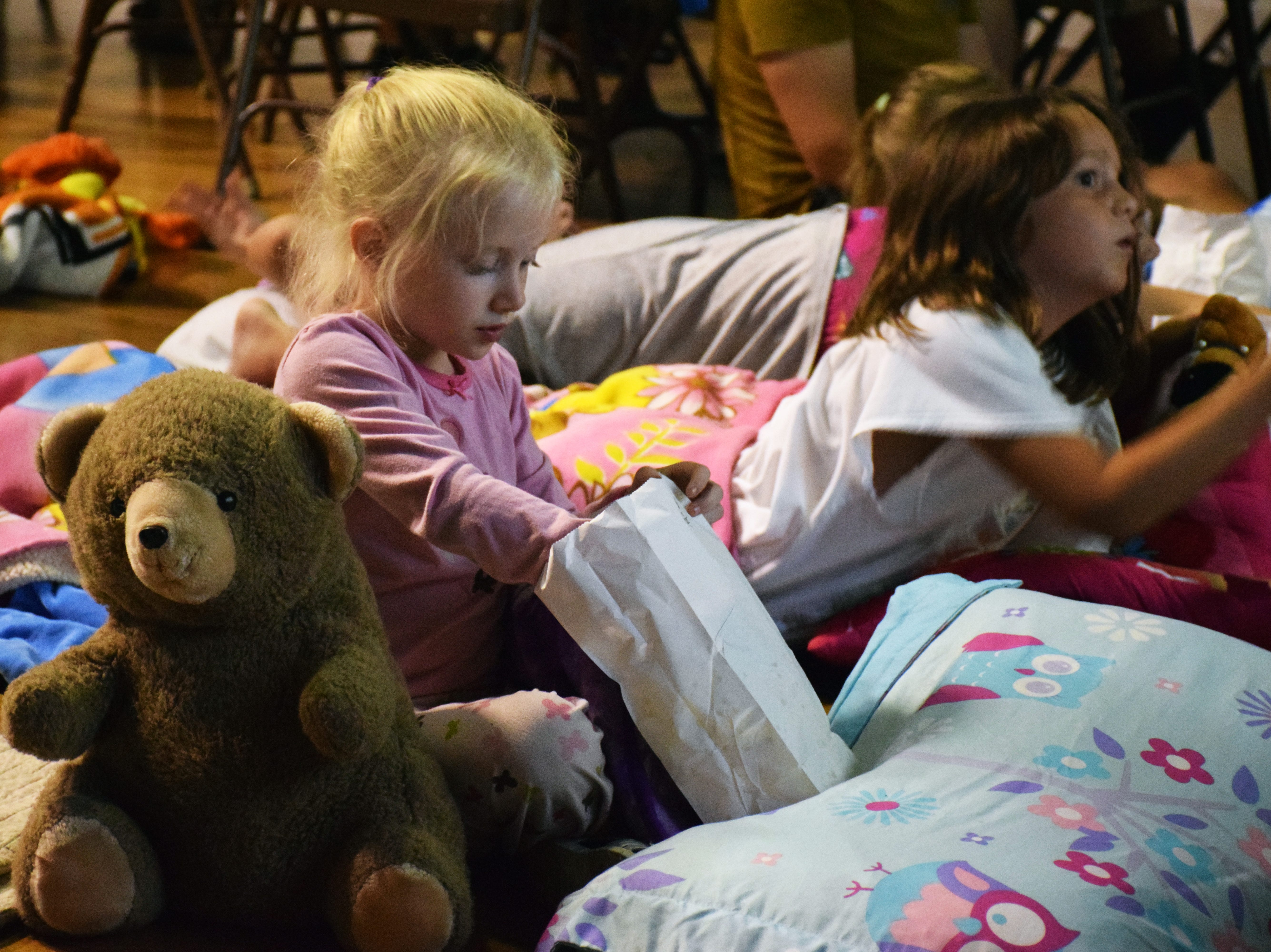 Little girl eating popcorn at the Moonshot Moment Pajama Pizza Party.