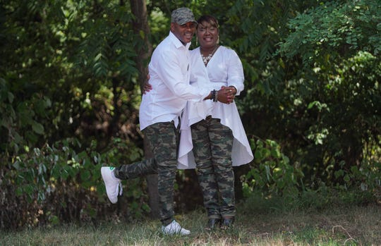 Pastor David Mills wears fatigue pants from the New Castle Farmers Market; white button-down top; and white Adidas Stan Smith sneakers. His wife Bernadette wears fatigue pants from the New Castle Farmers Market, waist-tie high-low top by ZARA; and black chunky heelplatform sandals by Michael Kors.