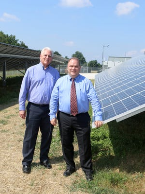 Delaware Municipal Electric Corporation (DEMEC) president and CEO Patrick McCullar and Smyrna town manager Gary Stulir stand next to solar panels at the Smyrna Solar Facility, which will deliver 1.5 megawatts of electric energy to residents and businesses in the town.