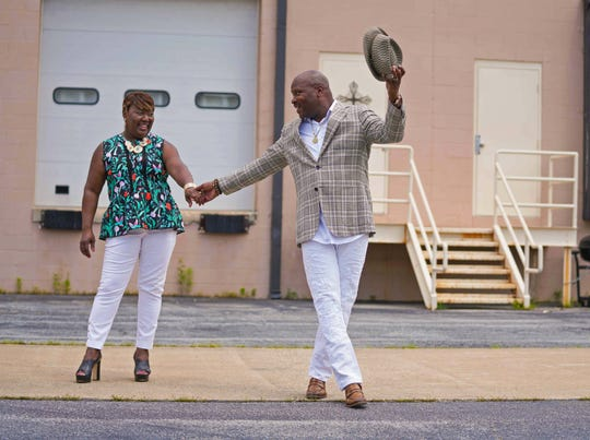 Pastor Bernadette Mills wears a black, green and orange peplum top by Kate Spade; white pants; and black platform sandals by Michael Kors. Her husband David wears a summer plaid blazer, white button-down shirt, white distressed jeans and Bailey's summer brim hat.