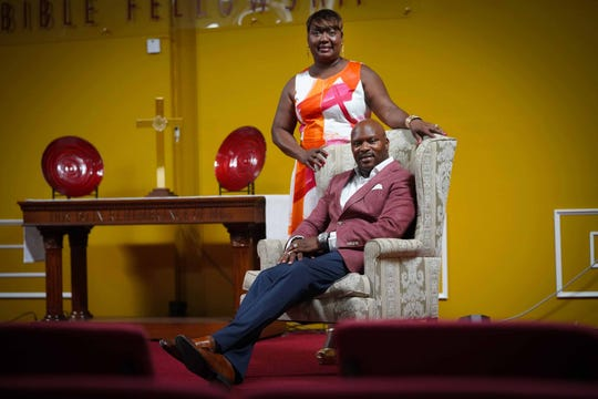 Pastor David Mills wears a raspberry blazer by Suit Supply; white button-down shirt; Calvin Klein blue dress pants and cognac Monk shoes. His wife, Bernadette, wears a fuchsia, orange and white dress by Calvin Klein with gold platform sandals by Michael Kors.