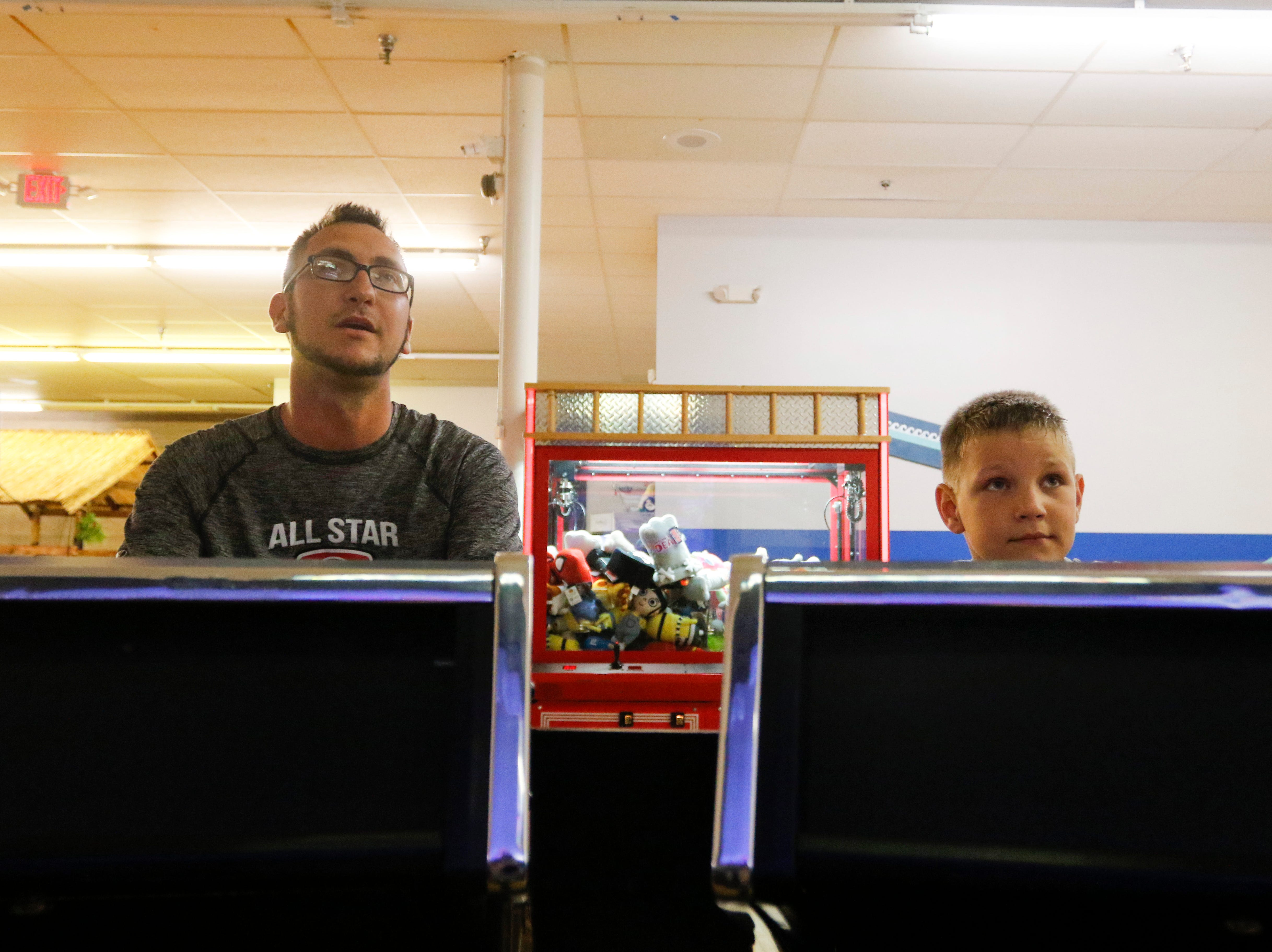 Chris Matijevic and his son Layton Kramer, 8, play a trivia game at Hub City Adventure Wednesday, July 18, 2018.