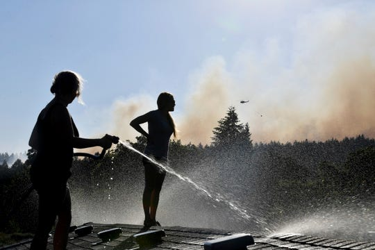 In this Tuesday, July 17, 2018 photo, Deidre Mallgren, left, hoses down the roof of her friend at right, Lindsey Bennett's home as helicopters attack a fast moving wildfire, in Spokane Valley, Wash.