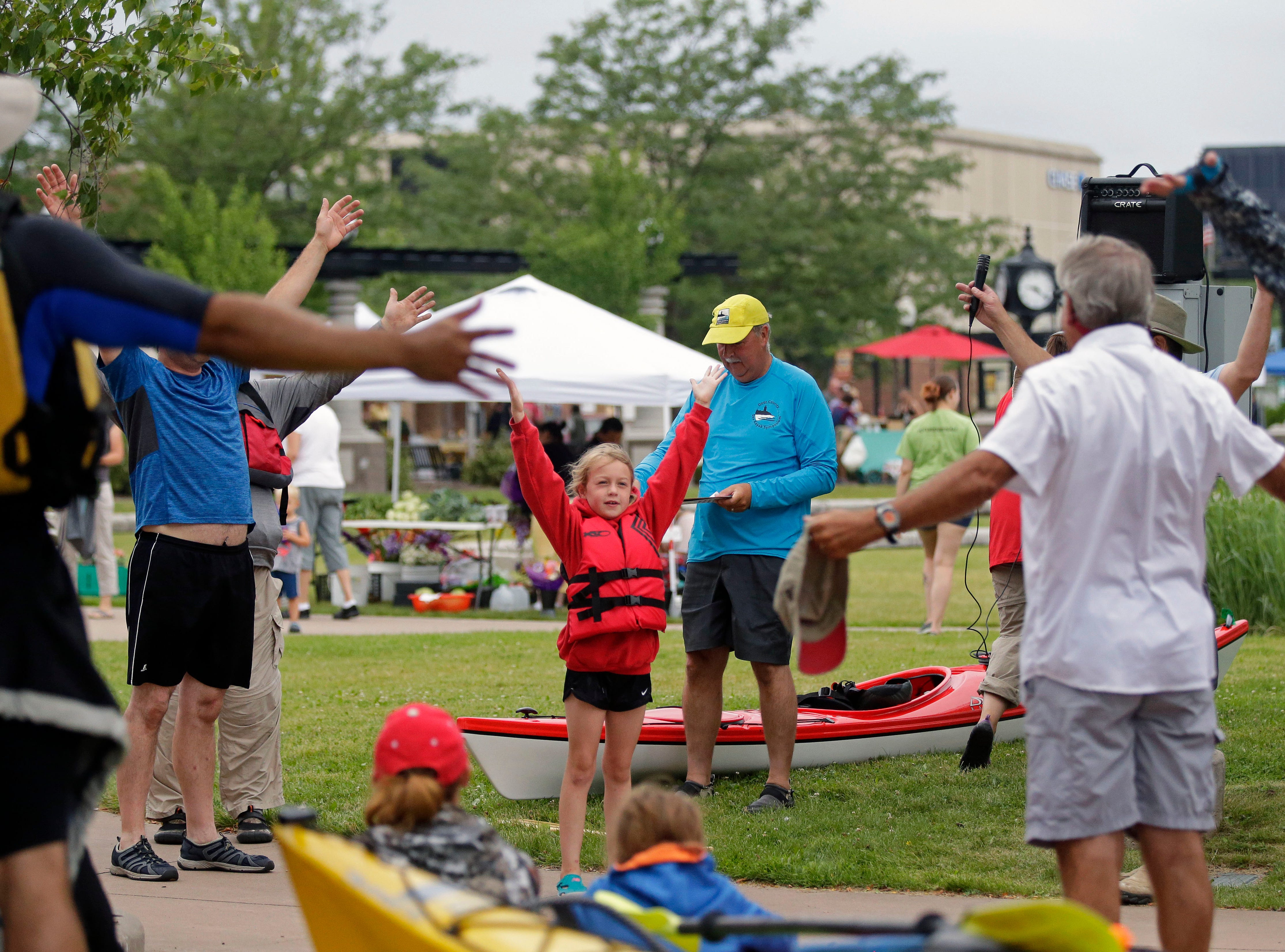 Ella Pynenberg leads kayakers in a stretch before the Park-to-Park Paddle get started Saturday, July 21, 2018, at Shattuck Park in Neenah, Wis.