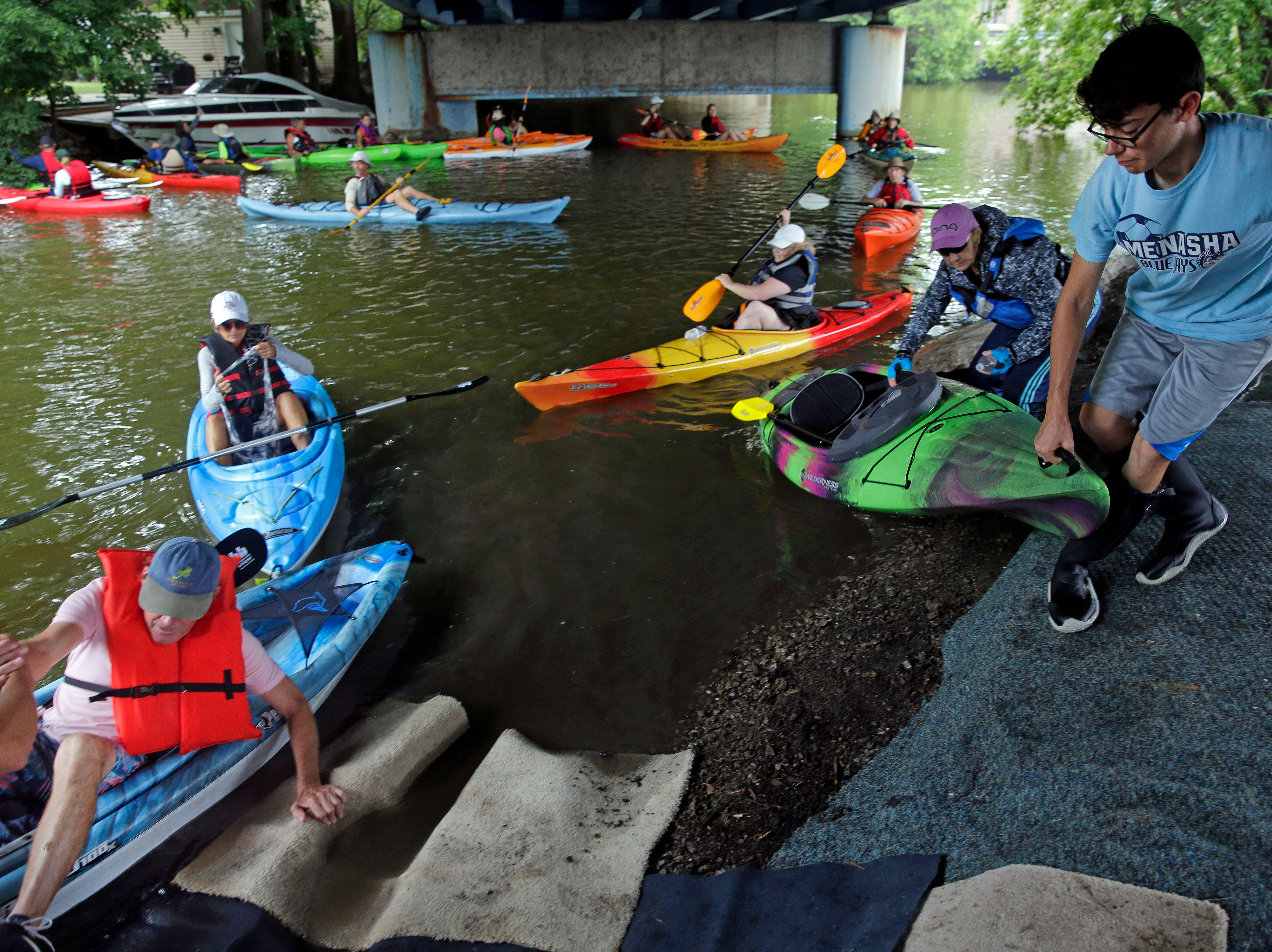 Members of the Menasha High School soccer team help with a portage as the Park-to-Park Paddle takes place Saturday, July 21, 2018, in Menasha, Wis.