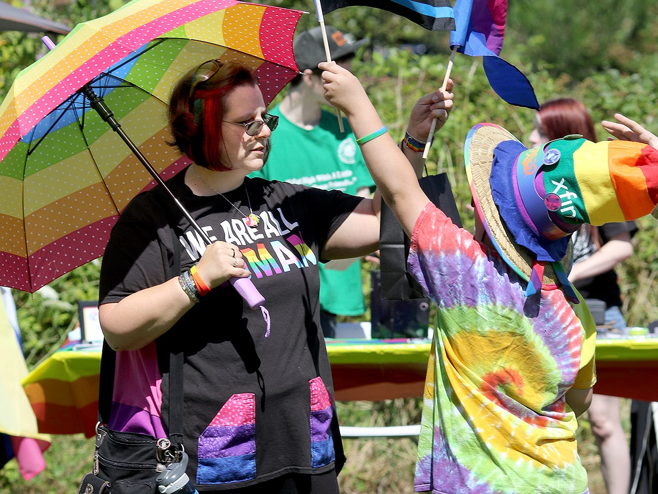 Dani Gainer and her son Jasper, 9, of Bremerton, wave their pride flags during the Kitsap Pride Festival on Saturday July, 21, 2018 at Evergreen-Rotary Park in Bremerton.