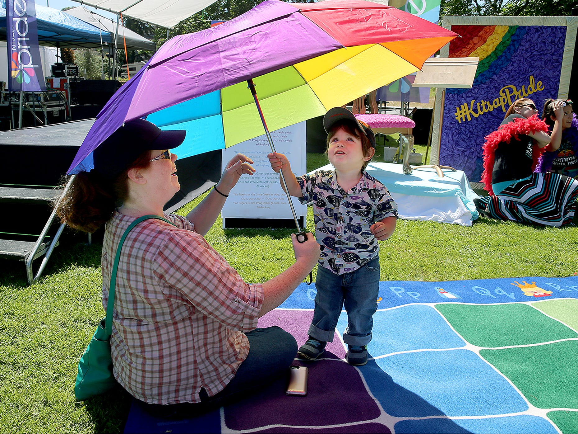 Bridget Morgan, of Bremerton, and her son Ronan, 2, stay in the shade on a hot day under a rainbow umbrella during the Kitsap Pride Festival on Saturday July, 21, 2018 at Evergreen-Rotary Park in Bremerton.