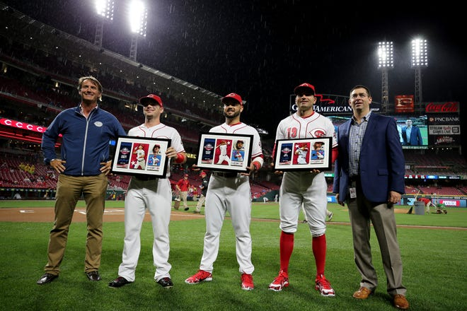 From left: Cincinnati Reds President of Baseball Operations Dick Willams, second baseman Scooter Gennett (3), third baseman Eugenio Suarez (7), first baseman Joey Votto (19) and General Manager Nick Krall pose for a pregame photo recognizing the team's All-Stars, Friday, July 20, 2018, at Great American Ball Park in Cincinnati.
