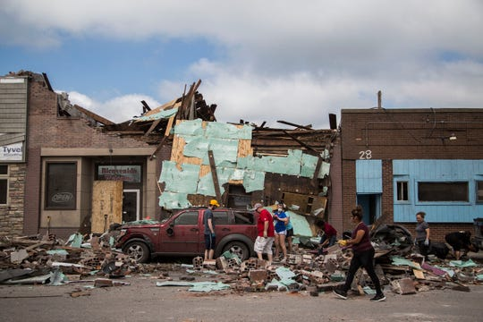 A group of people work to clear rubble surrounding a car in downtown Marshalltown on Saturday, July 21, 2018, two days after a devastating tornado blew through the city.