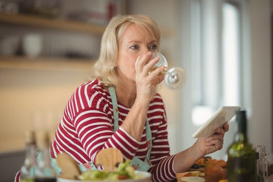Senior Woman Drinking Wine While Holding Digital Tablet