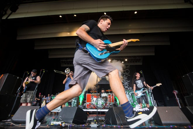 Less Than Jake guitarist Chris Demakes runs across the Journeys Right Foot stage during Vans Warped Tour at Meadow Brook Amphitheatre on Friday, July 20, 2018, in Rochester Hills.