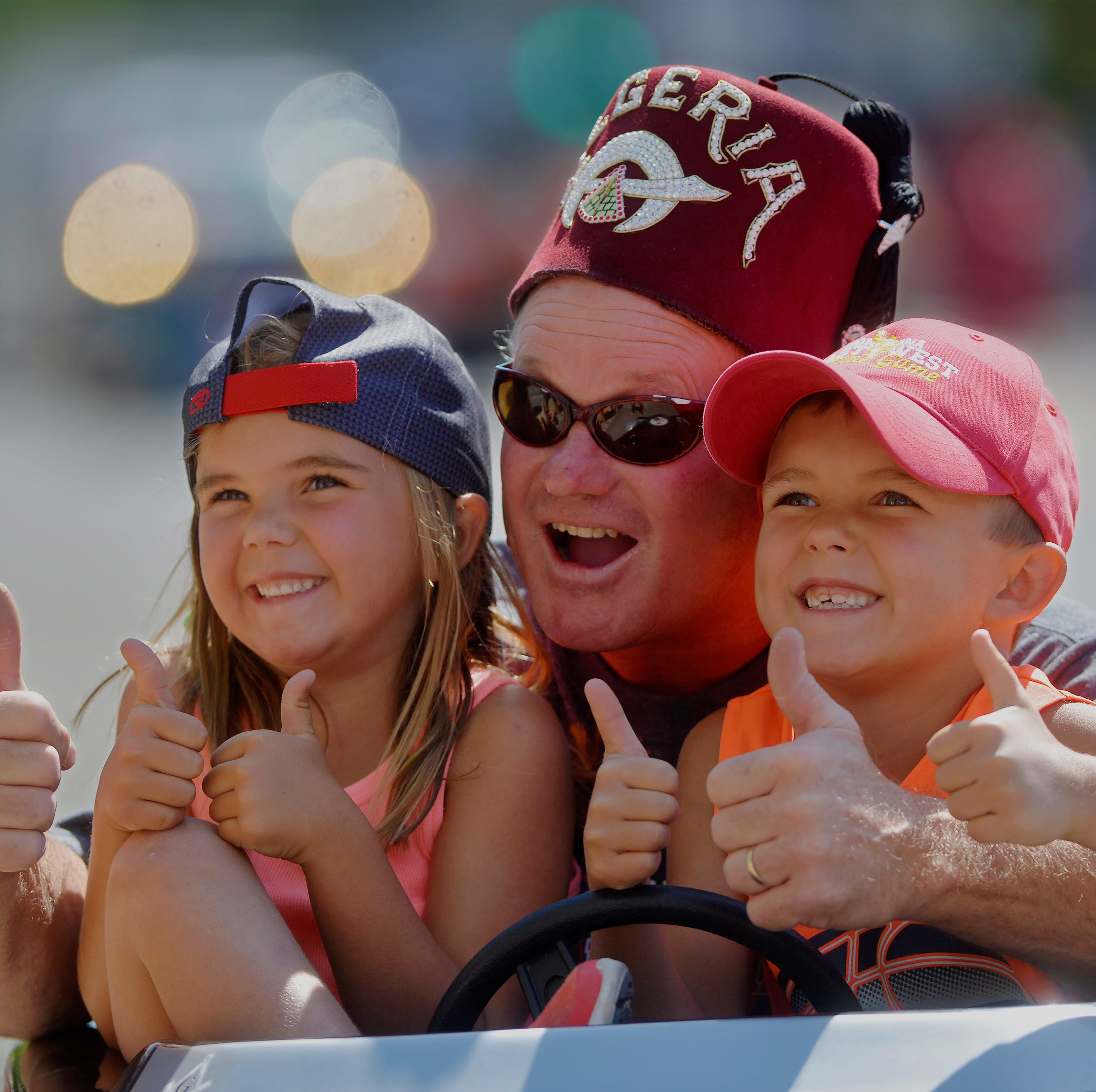 Jerzi, left, and Jett Nichols pose with Shriner Joe Sidor in a mini-car during the Montana East West Shrine Game Parade on Central Avenue, Saturday morning.  The East and West teams made up of all-star high school football players from around the state will be played Saturday night at Memorial Stadium at 7 p.m.