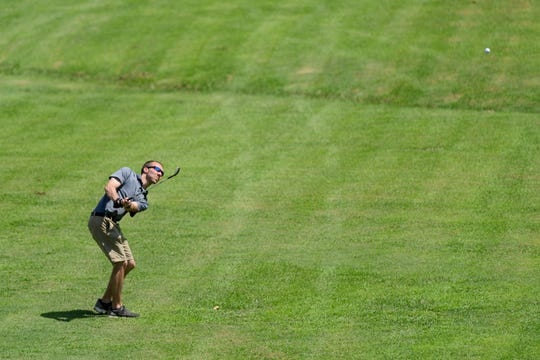 Isaac Church hits along the fairway of hole five during the first round of the Jace Bugg Men's City Golf Tournament at Henderson Municipal Golf Course in Henderson, Ky., Saturday, July 21, 2018.