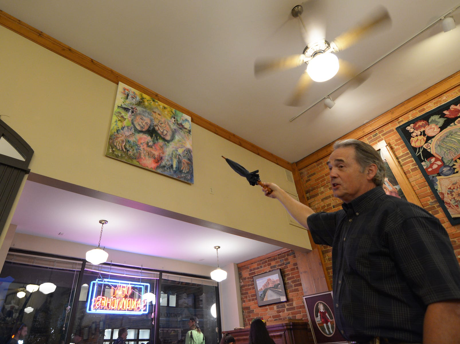 Chris Ryckman gestures with an umbrela, former co-owner of the Four Reasons Bakery and Deli, explains a painting he created inspired by the milestones of his parents marriage Friday, July 20, 2018, during the Lancaster Festival ArtWalk.