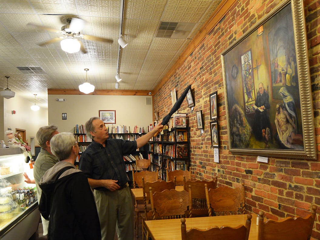 """Chris Ryckman former co-owner of the Four Reasons Bakery and Deli gestures with an umbrella as he explains the story behind his painting """"The Preserver"""" Friday night, July 20, 2018, during the Lancaster Festival ArtWalk."""