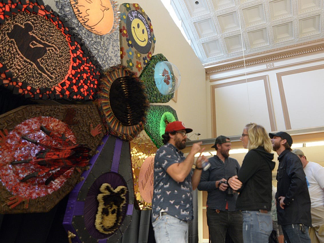 """Cuban artist Lorenzo Lopez Shening talks about his sculpture """"Love Me, Love Me Not"""" on display at Fairfield National Bank Friday evening, July 20, 2018, during the Lancaster Festival ArtWalk."""