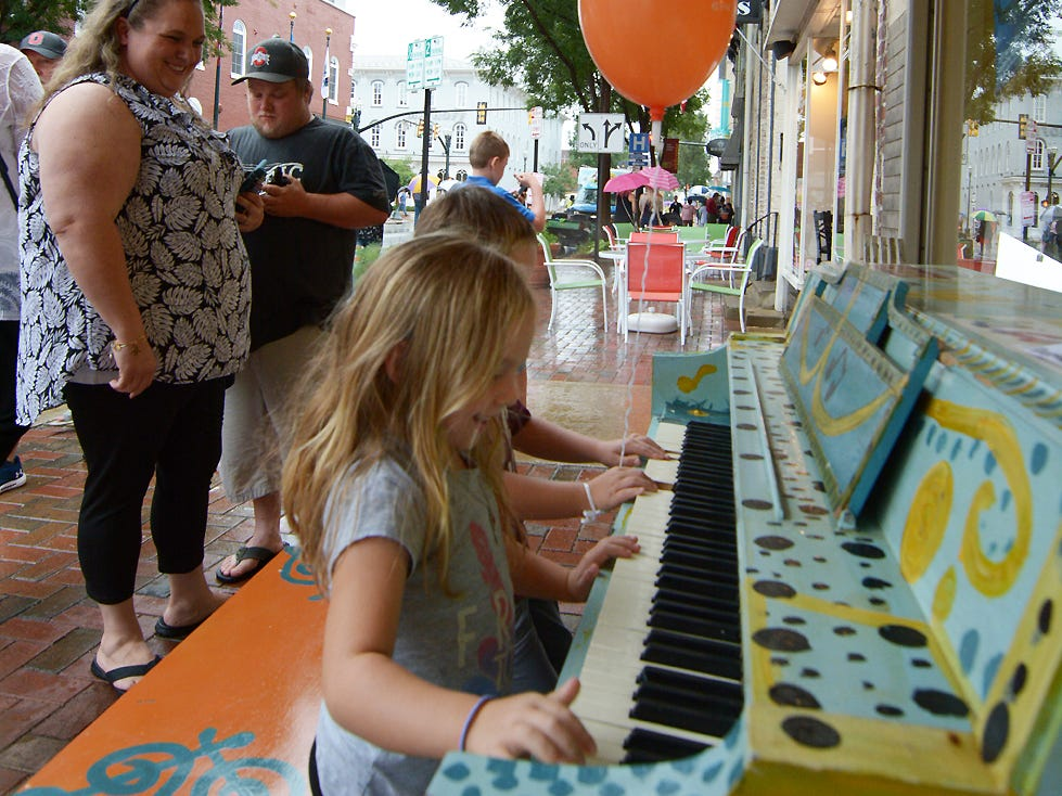 Emily and Nicholas Scott play the piano under an awning in the rain Friday afternoon, July 20, 2018, during the Lancaster Festival ArtWalk.