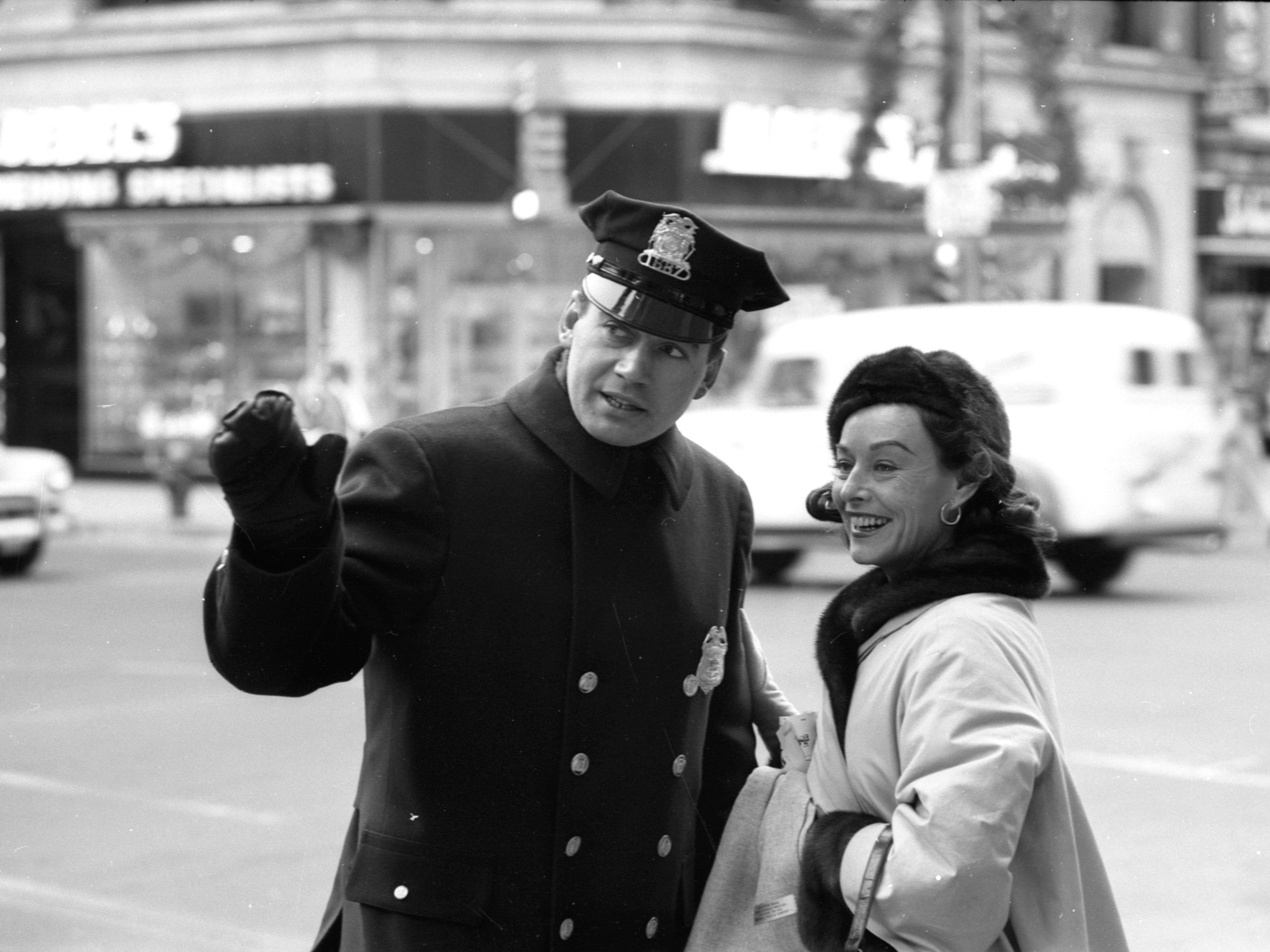 "Actress Paulette Goddard asks Milwaukee police officer Leland Sande for directions on W. Wisconsin Ave. on Dec. 3, 1957. Goddard, whose Hollywood credits included the Chaplin movies ""Modern Times"" and ""The Great Dictator"" and the World War II drama ""So Proudly We Hail,"" was in town to perform in the comedy ""Waltz of the Toreadors"" with Melvyn Douglas at the Pabst Theater. This photo was published in the Dec. 4, 1957, Milwaukee Journal."