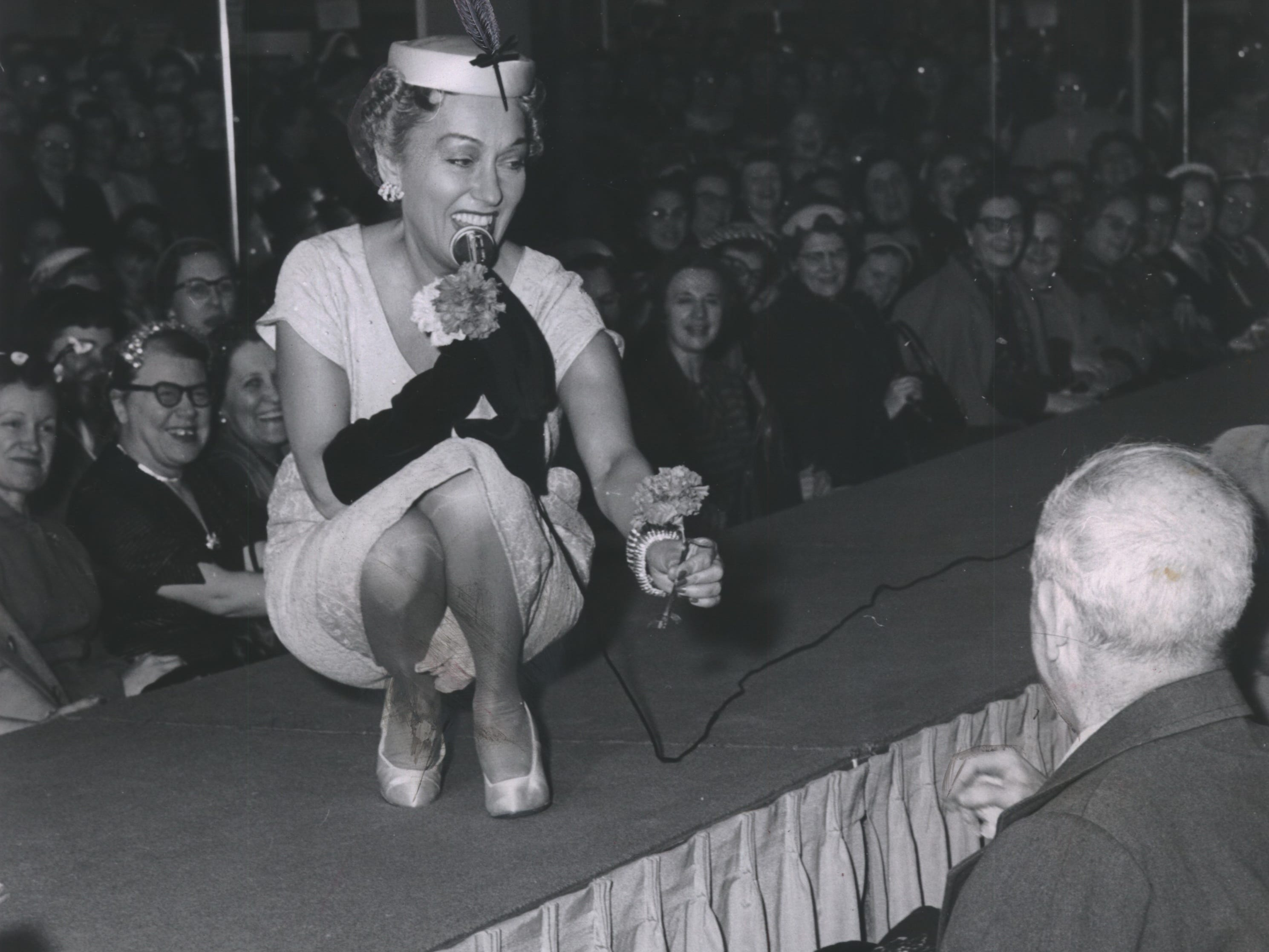 "Actress turned fashion designer Gloria Swanson offers a rose to an admirer during a fashion show at Schuster's department store on N. 3rd St. (now King Drive) at Garfield Ave. on March 16, 1954. Swanson, who three years earlier was nominated for an Oscar for her performance in ""Sunset Boulevard,"" led two style shows at the popular department store that day. This photo was published in the March 17, 1954, Milwaukee Journal."