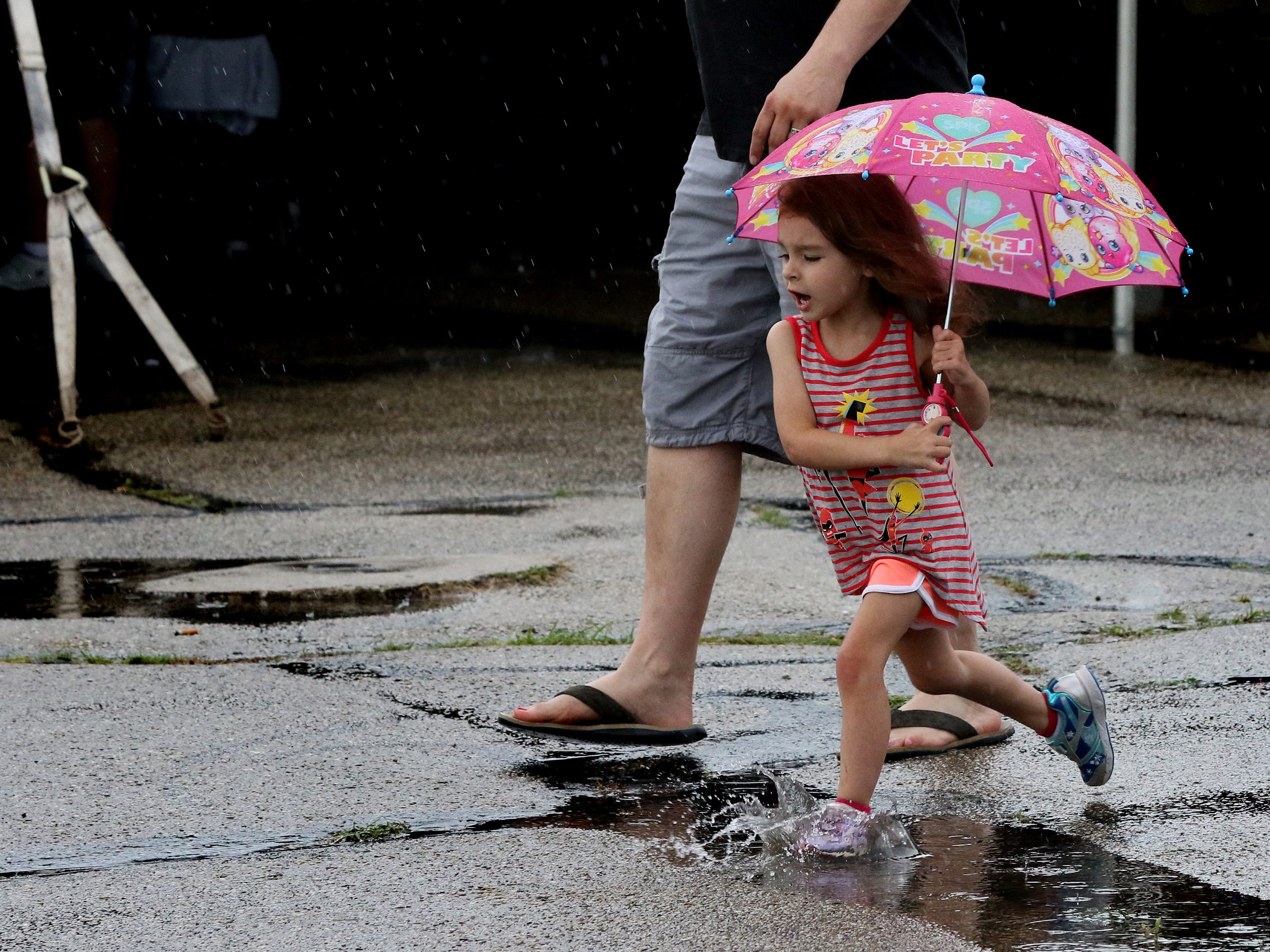 Britney Weinstein, 4, works her way through puddles as rain dampenes the opening night of the Cudahy Lions Sweet Apple-Wood Festival at Cudahy Park on July 20.