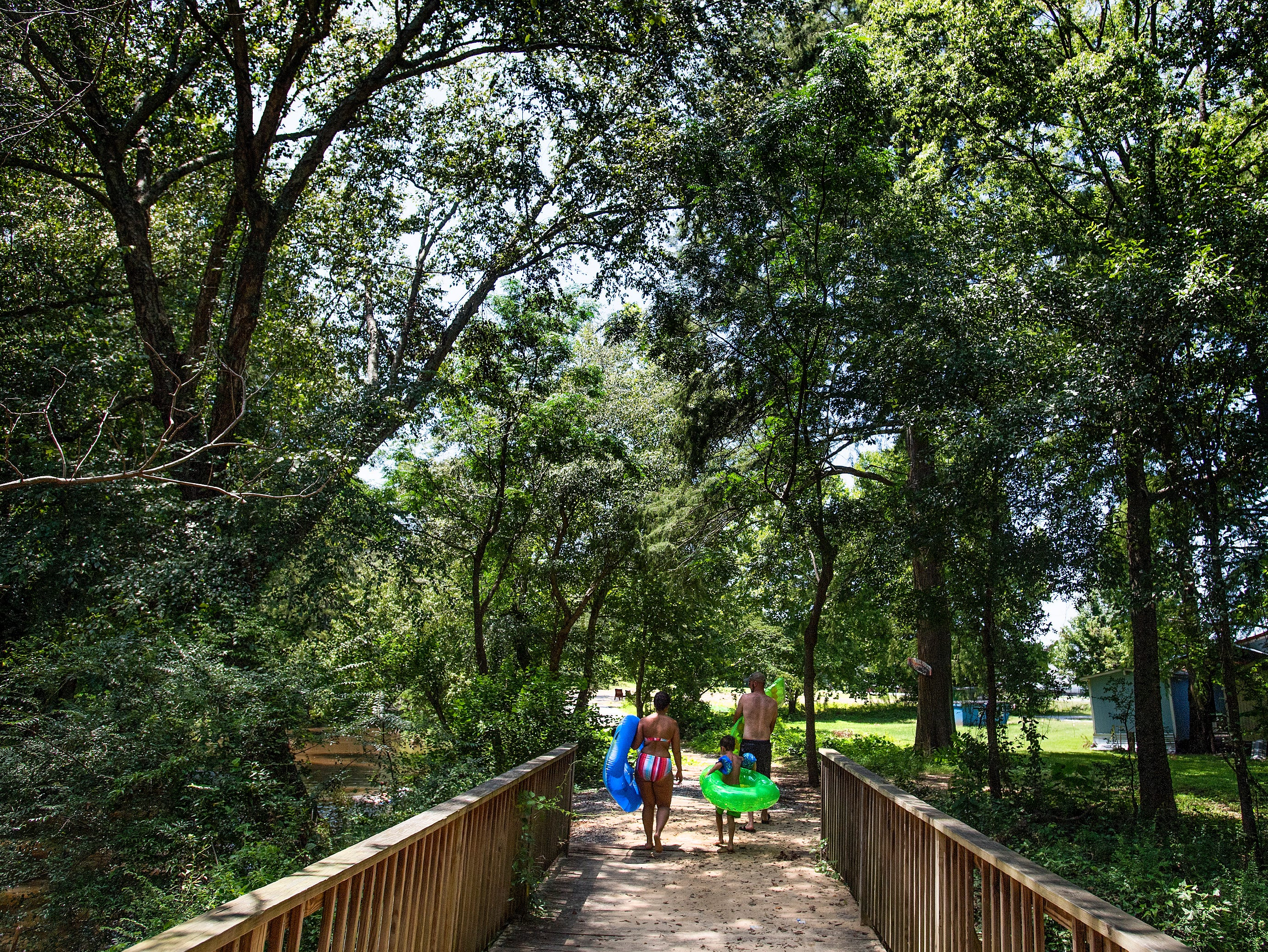 Blake Bailey, Coen Bailey and Cassandra George walk beside Autauga Creek in Prattville, Ala., on Saturday, July 21, 2018.