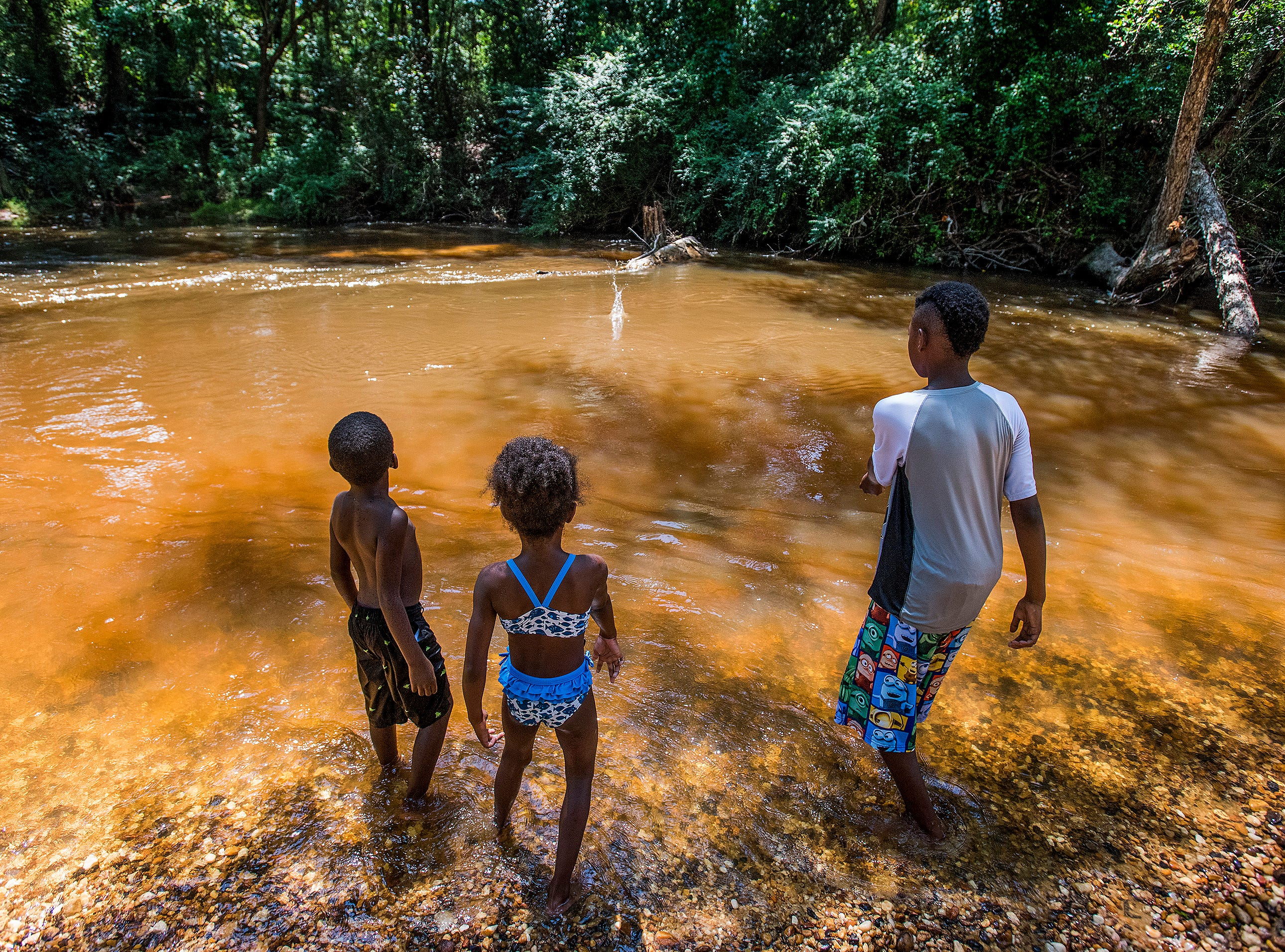 Aiden Dennis, Miracle Taylor and Jeremiah Smiley throw rocks in Autauga Creek in Prattville, Ala., on Saturday, July 21, 2018.
