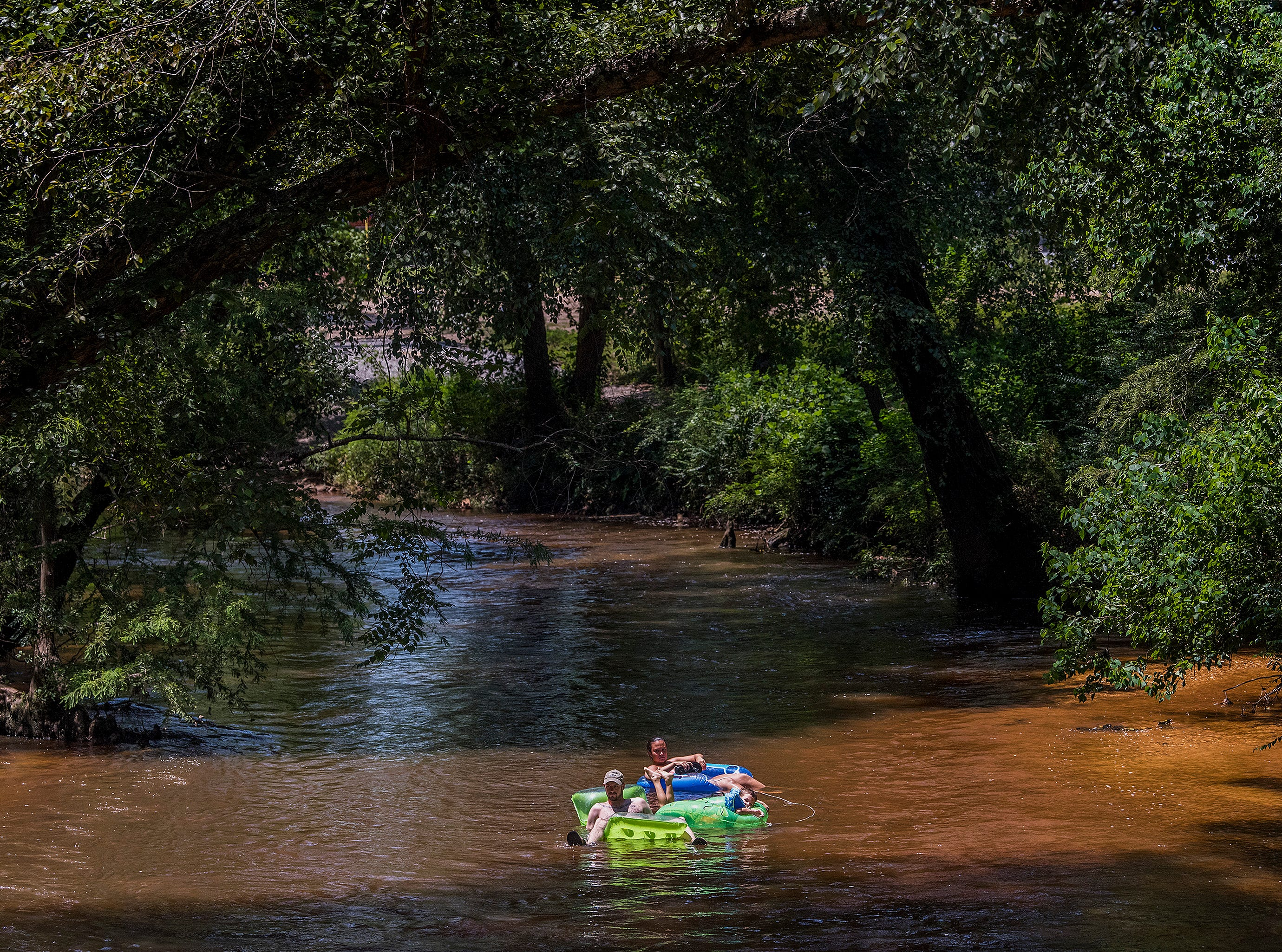 Blake Bailey, Coen Bailey and Cassandra George float down Autauga Creek in Prattville, Ala., on Saturday, July 21, 2018.