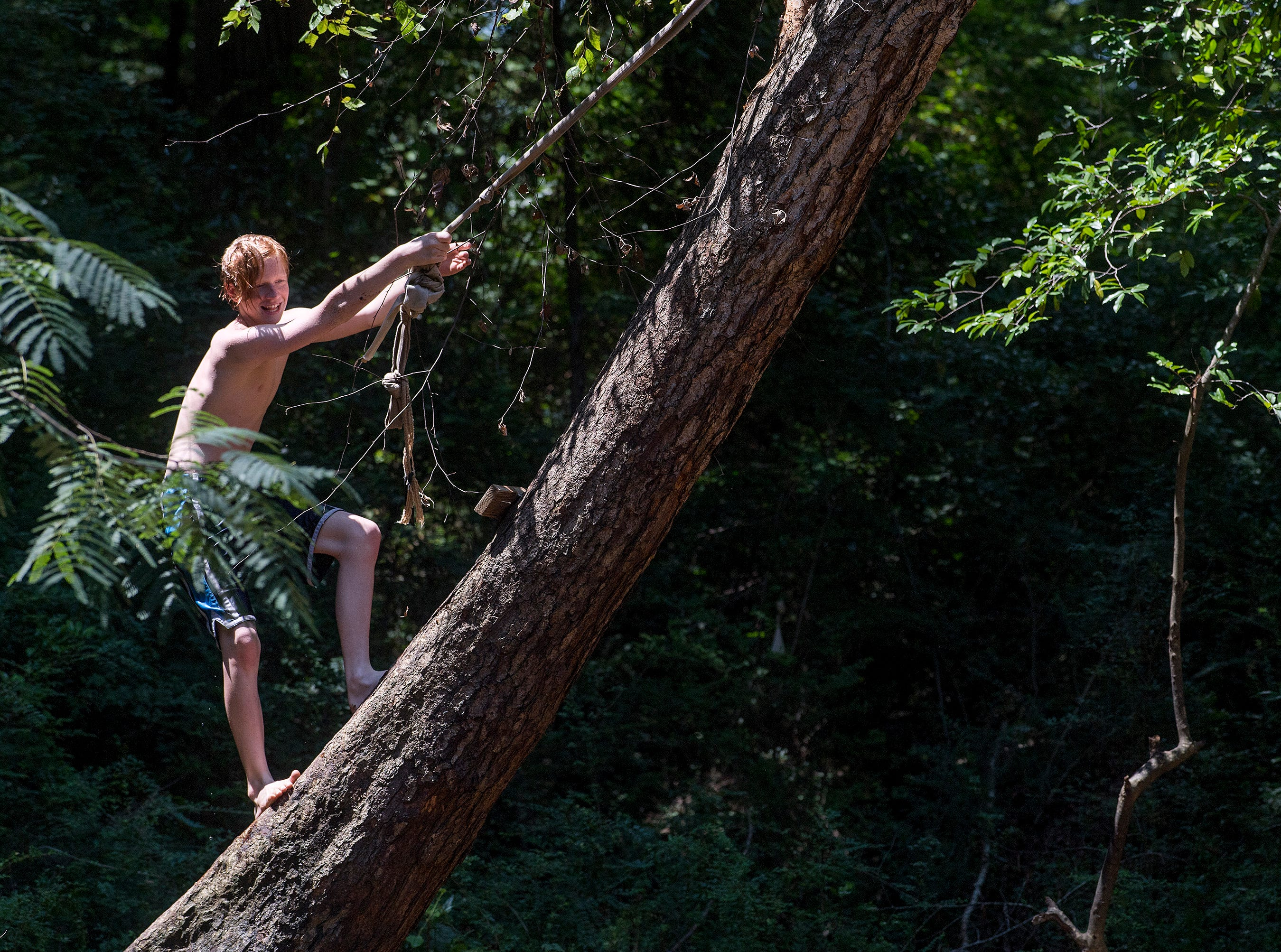 Caleb Eady plays on a rope swing on Autauga Creek in Prattville, Ala., on Saturday, July 21, 2018.