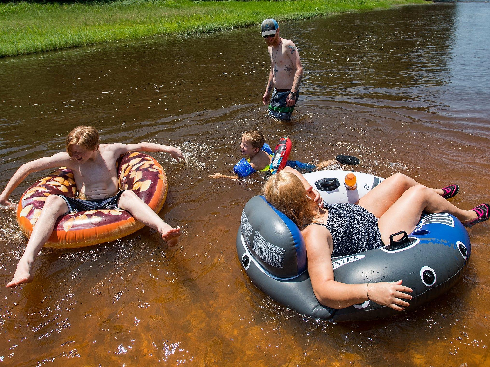 Caleb Eady, from left, Sawyer Sims, Chris Thomas and Karson Smith float on  Autauga Creek in Prattville, Ala., on Saturday, July 21, 2018.