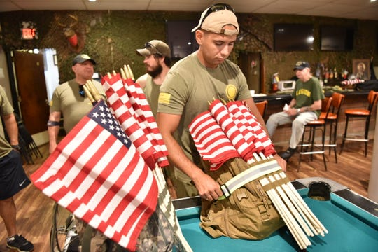 Michael Adis, Corporal, USMC, straps a bunch of US flags on his pack. The Woodland Park American Legion members took on a 5K march on Saturday to visit the elderly veterans who are unable to make it to the post themselves, and to post and replace US flags along the route.