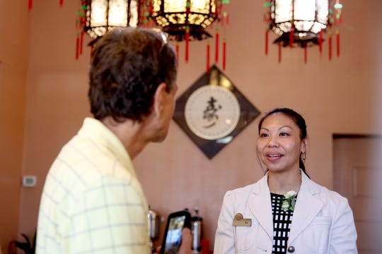 Ket Kwan, the daughter of Kam Sang Kwan, speaks with Kris Dunn, 65, of Albany, during a celebration of life honoring Kam Sang Kwan at Kwan's Original Cuisine in Salem on Saturday, July 21, 2018. The beloved Salem chef died June 17 at 82 years old.