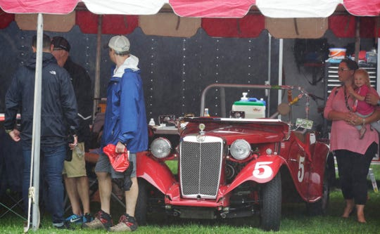 People seek shelter under a tent along with a vintage MG race car during the WeatherTech International Challenge with Brian Redman at Road America, Saturday, July 21, 2018, at Elkhart Lake, Wis.