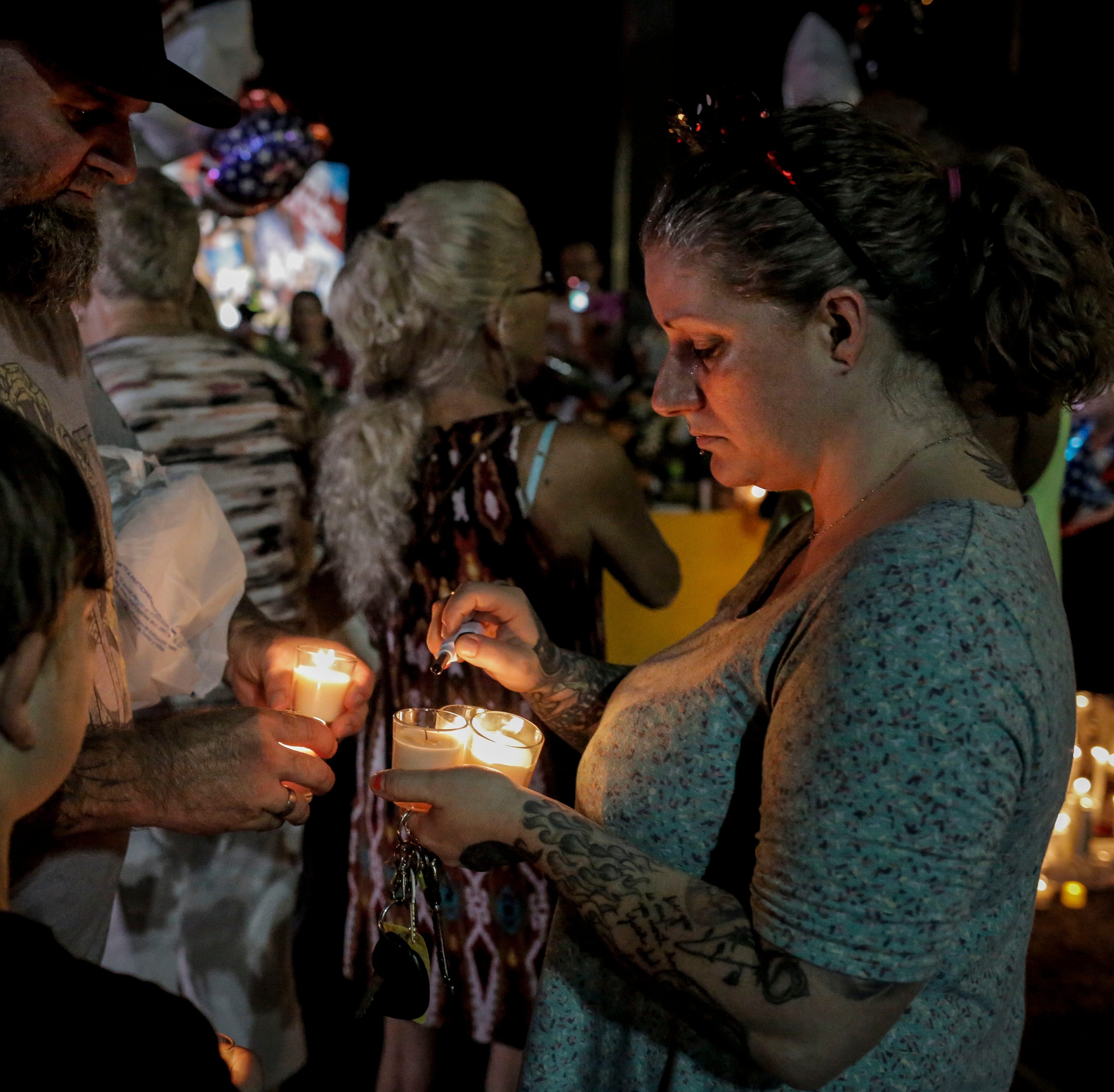 Shana Hamil, right, and Josh Hamil, left, light candles during a vigil in the parking lot outside Ride the Ducks in Branson, Mo. on Friday, July 20, 2018. On Thursday, July 19, 2018, 17 people were killed when a duck boat, an amphibious vehicle, capsized on Table Rock Lake.
