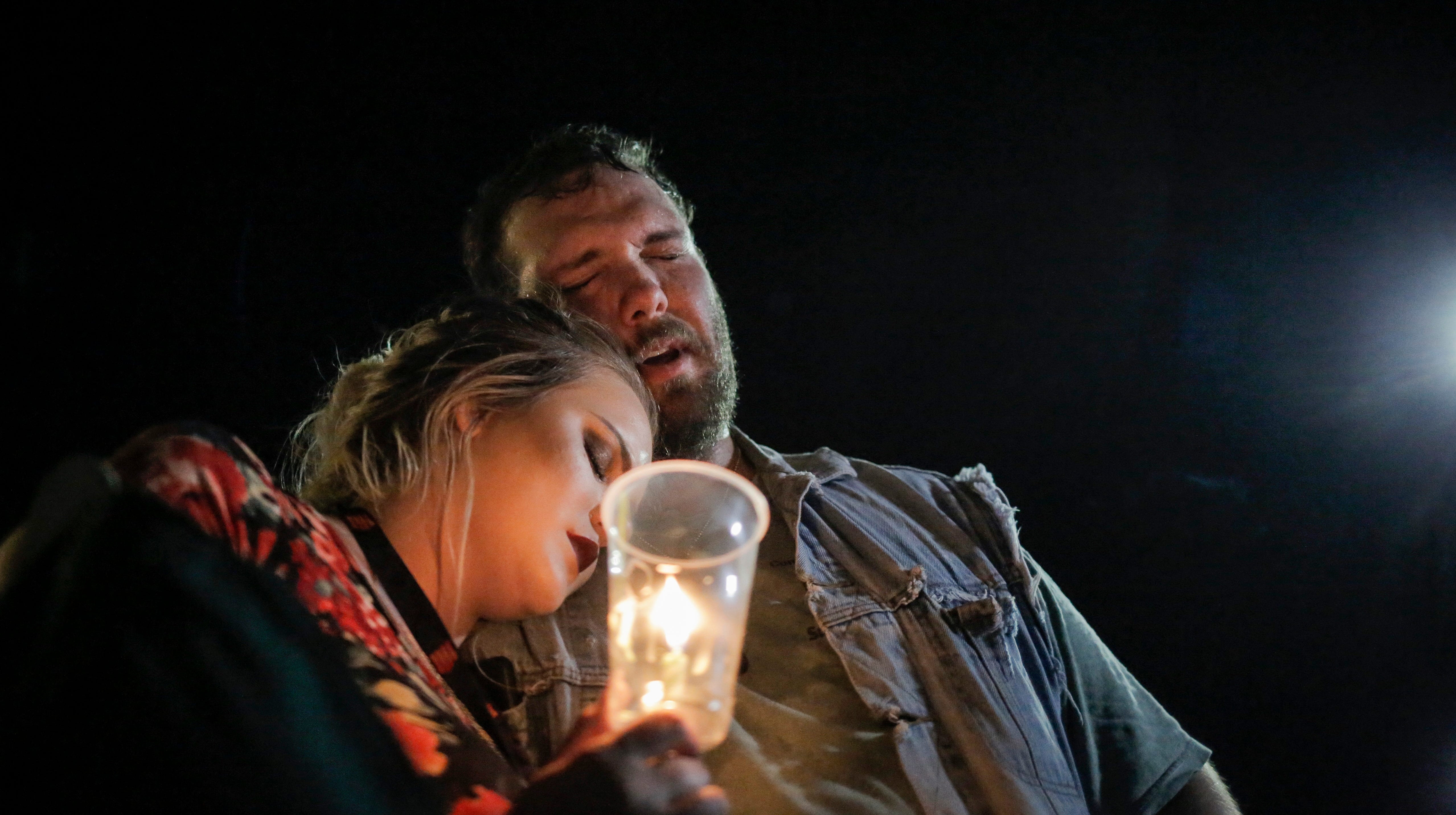 """Robert Montgomery of Branson, left, sings """"Amazing Grace"""" along with hundreds of community members gathered in the parking lot outside Ride the Ducks, lighting candles and placing flowers on the cars of two victims from the duck boat accident in Branson, Mo. on Friday, July 20, 2018. On Thursday, July 19, 2018, 17 people were killed when a duck boat, an amphibious vehicle, capsized on Table Rock Lake."""