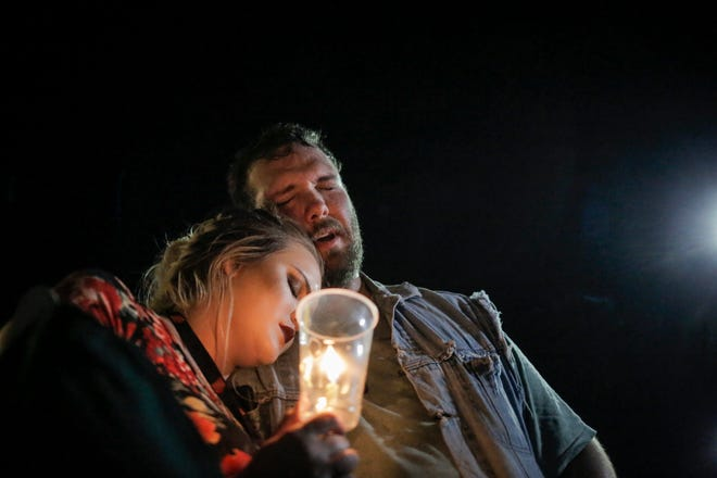 "Robert Montgomery of Branson, left, sings ""Amazing Grace"" along with hundreds of community members gathered in the parking lot outside Ride the Ducks, lighting candles and placing flowers on the cars of two victims from the duck boat accident in Branson, Mo. on Friday, July 20, 2018. On Thursday, July 19, 2018, 17 people were killed when a duck boat, an amphibious vehicle, capsized on Table Rock Lake."