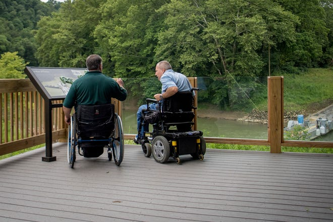 David Allgood and Tom Stokes overlook the Green River from a trail adapted for persons with disabilities at Mammoth Cave National Park in Cave City, Ky., Friday, June 22, 2018.  National Park Service accessibility chief Jeremy Buzzell says nine parks across the U.S. have received more than $10 million in federal funding to design and build accessibility projects as examples for other parks.