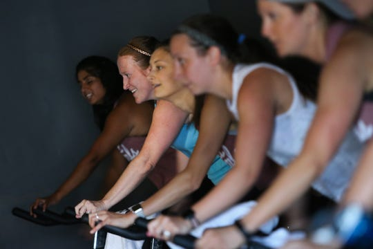 Riders go through a spin class at The Stables Spin Studio in Middletown Friday.