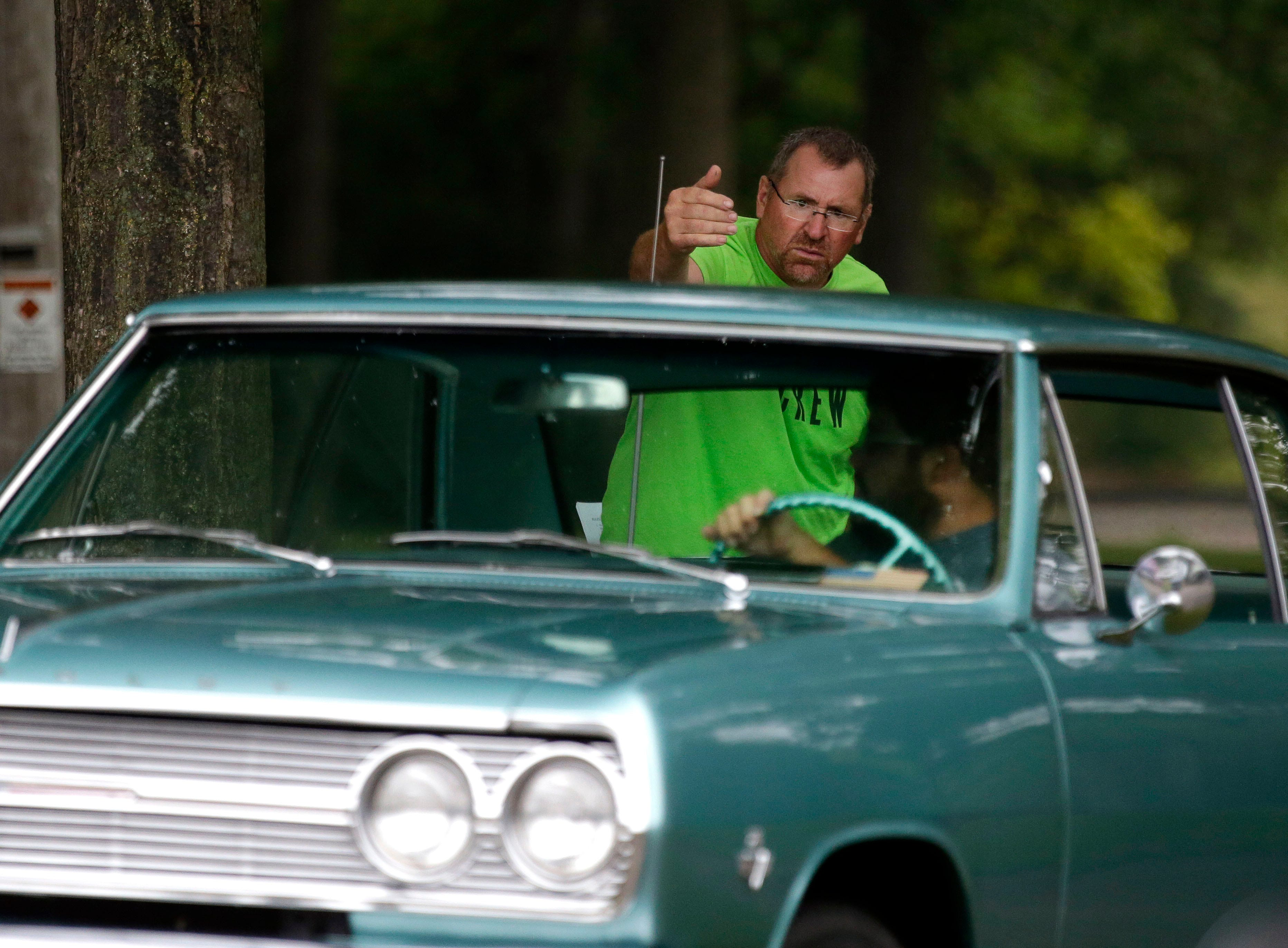 Randy Weiland directs Jeff Brecklin as he parks his car during the Appleton Old Car Show and Swap Meet Sunday, July 22, 2018, at Pierce Park in Appleton, Wis.