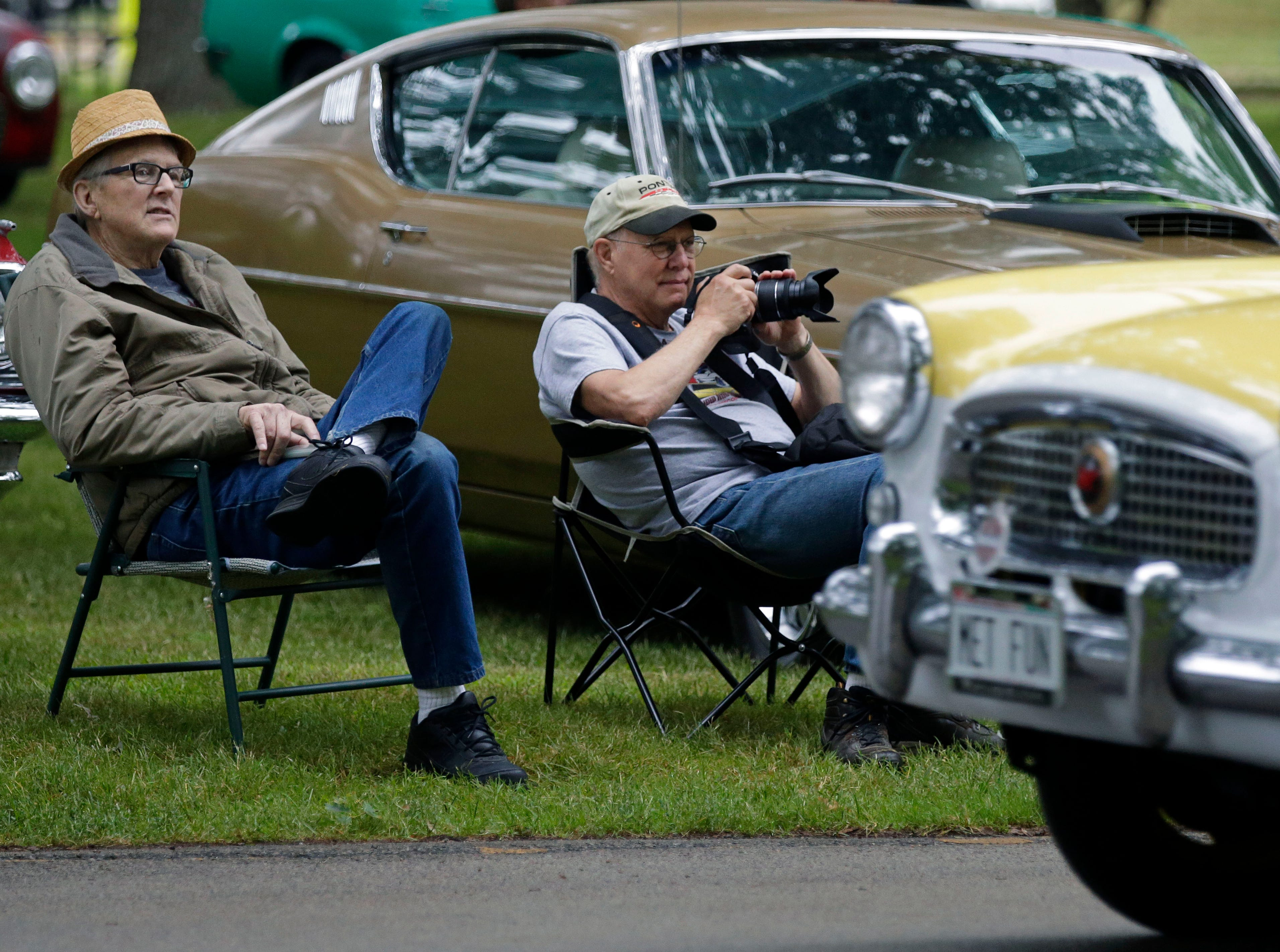 Wayne Weckwerth, left and Stan Feavel watch as cars arrive during the Appleton Old Car Show and Swap Meet Sunday, July 22, 2018, at Pierce Park in Appleton, Wis.