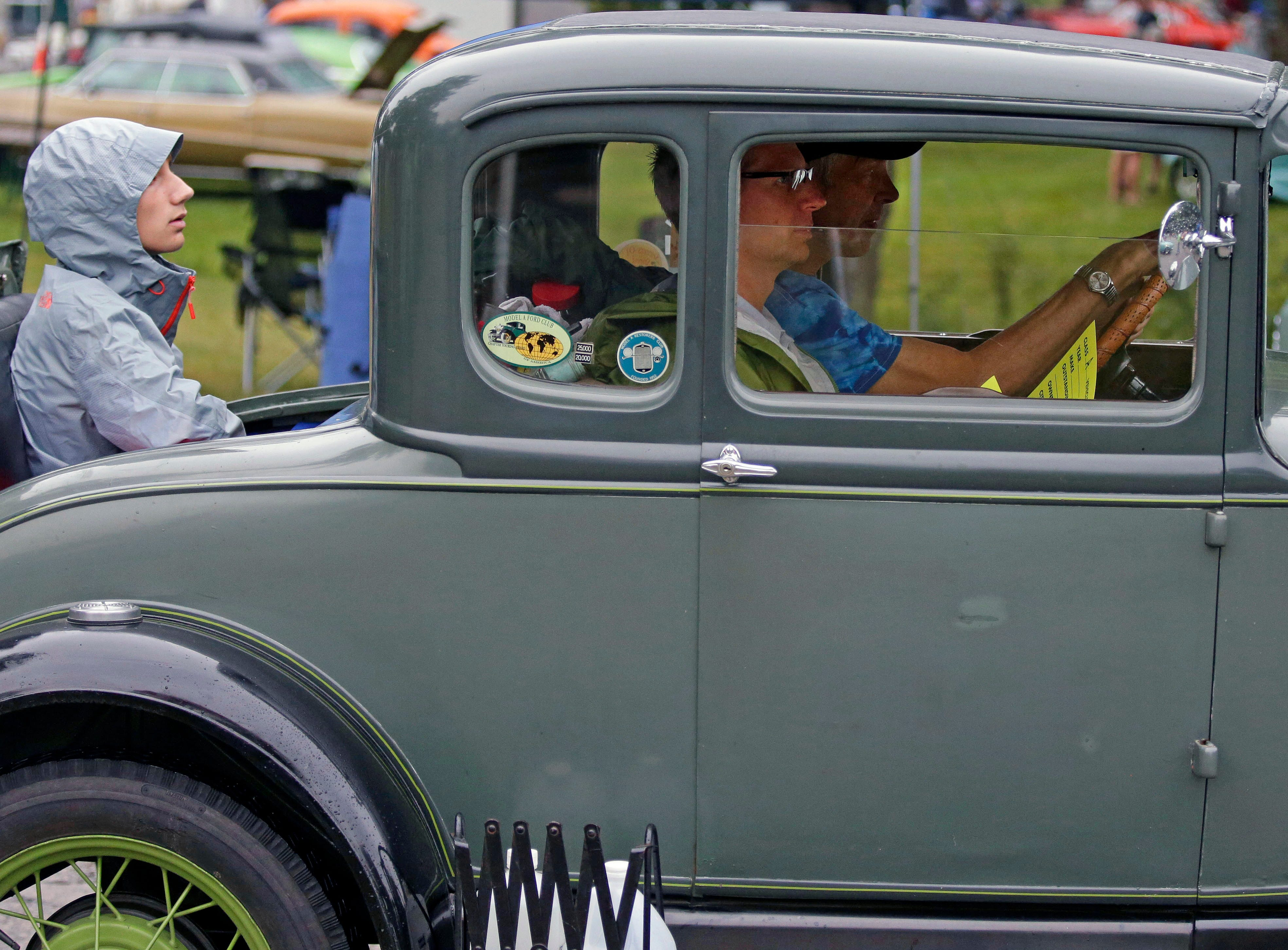 Dick Ziegert drives a Model A along with passengers Andy Ziegert, front, and Zachary Ziegert in the rumble seat during the Appleton Old Car Show and Swap Meet Sunday, July 22, 2018, at Pierce Park in Appleton, Wis.