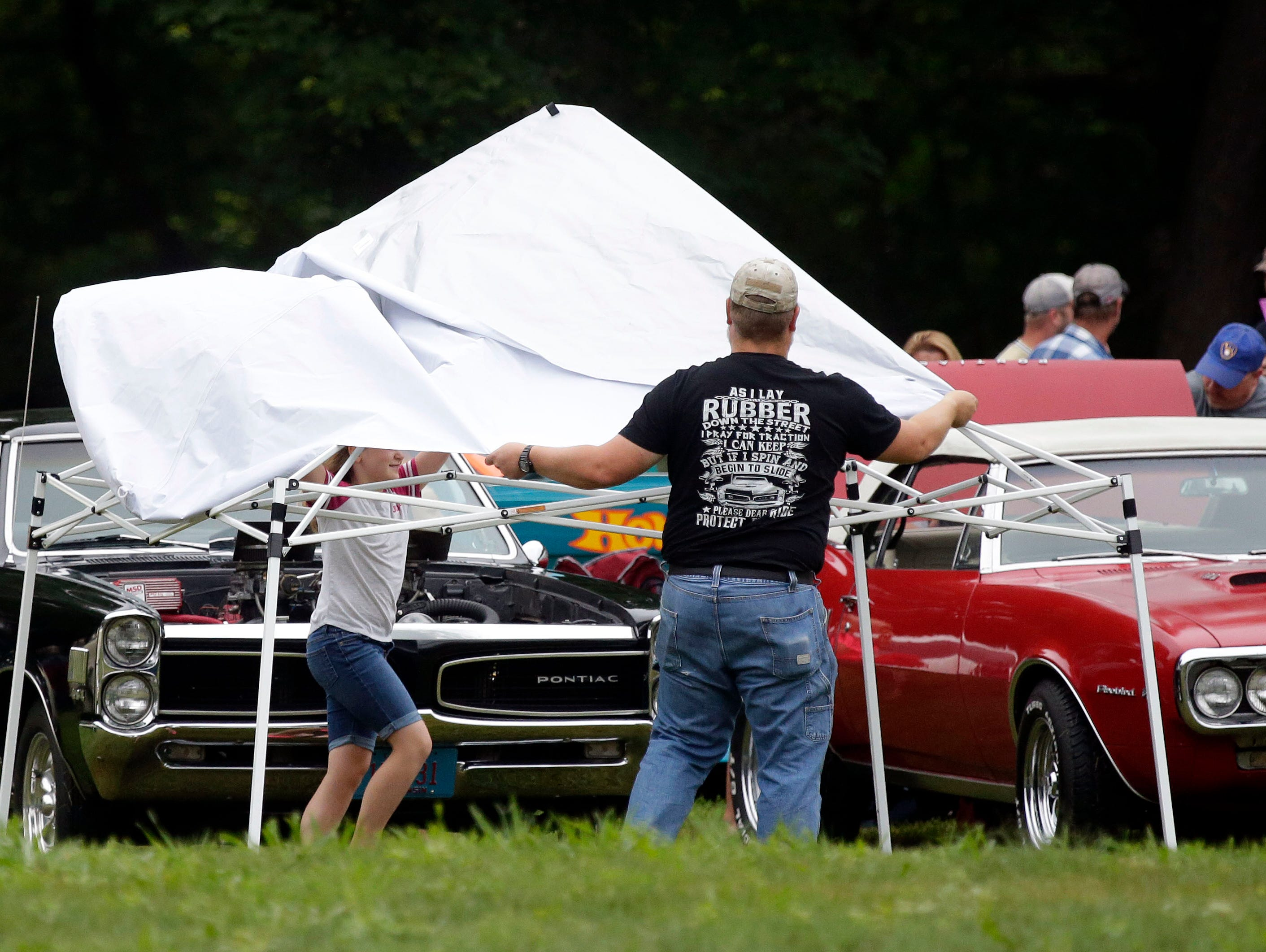 Andy Nelson gets help from his daughter, Kali, as they unfold a canopy during the Appleton Old Car Show and Swap Meet Sunday, July 22, 2018, at Pierce Park in Appleton, Wis.