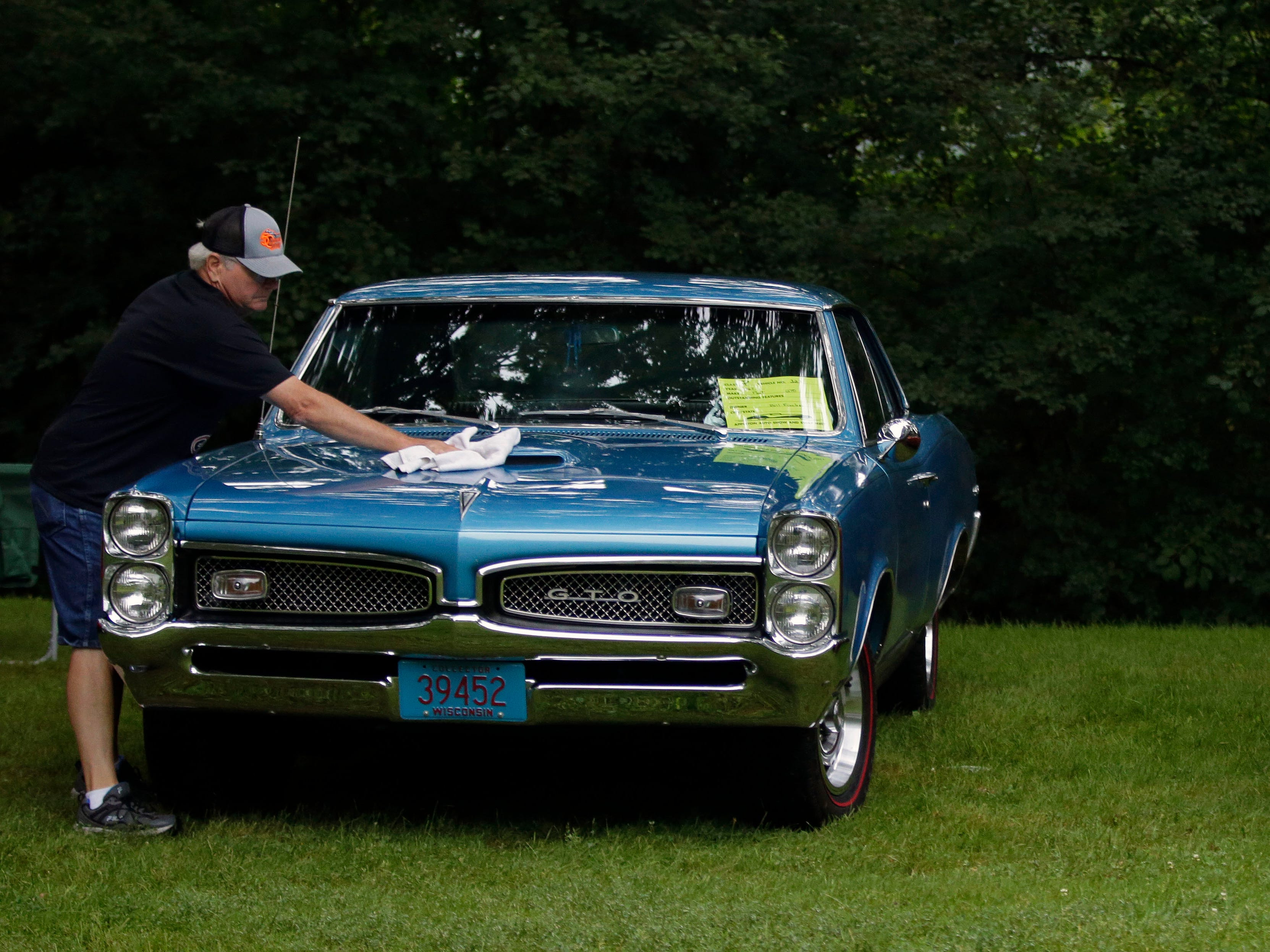 Bill Fischer, left, and Ronn Elliott, clean their cars as the Appleton Old Car Show and Swap Meet takes place Sunday, July 22, 2018, at Pierce Park in Appleton, Wis. Fischer has owned the 1967 GTO since 1970 and has not missed an Appleton car show in 41 years.